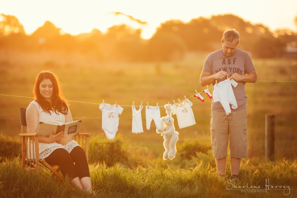 Pregnant mother sets up a clothes line with cute baby clothes and sets dad to work