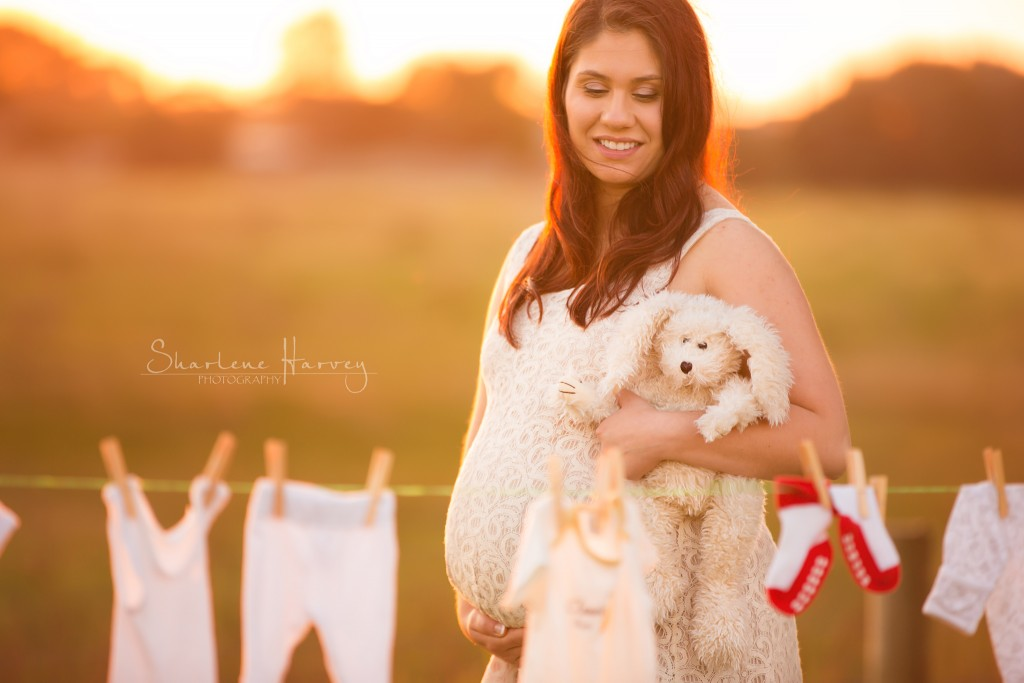 Glow Pregnant Mother poses in front of baby clothes - Mornington Peninsula Pregnancy Photographer