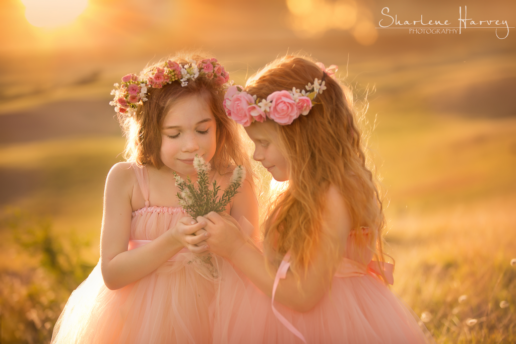 Gorgeous Girls in sunlight smelling flowers
