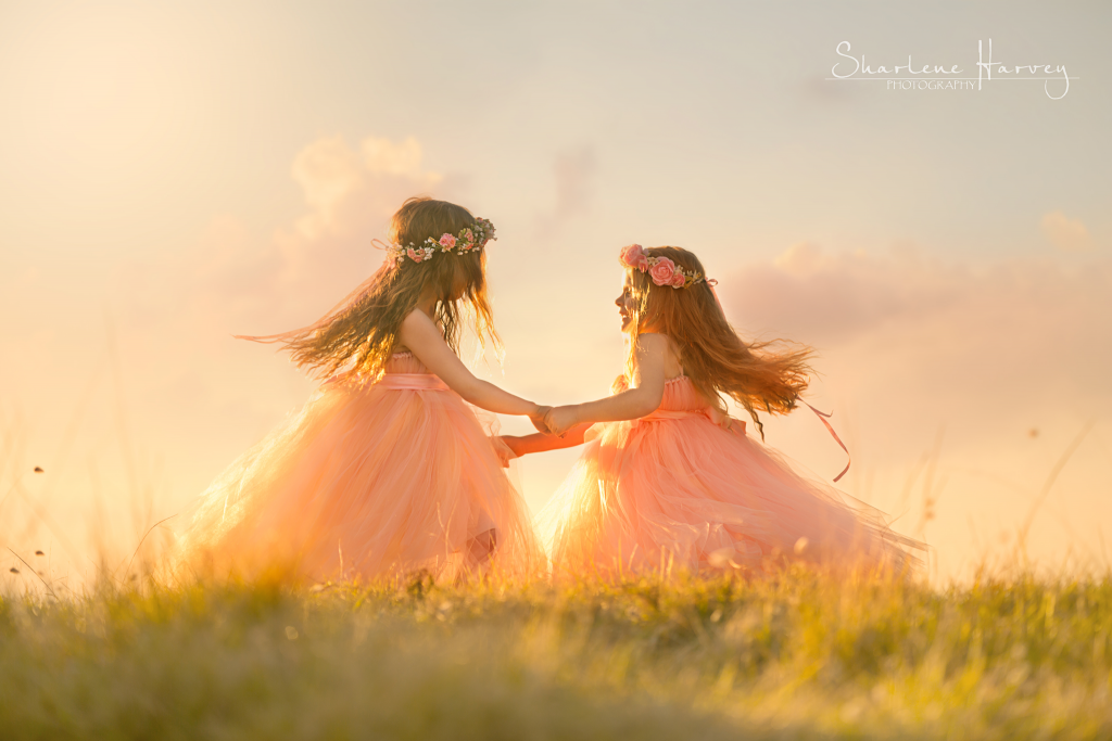 Two girls skipping together on a hill