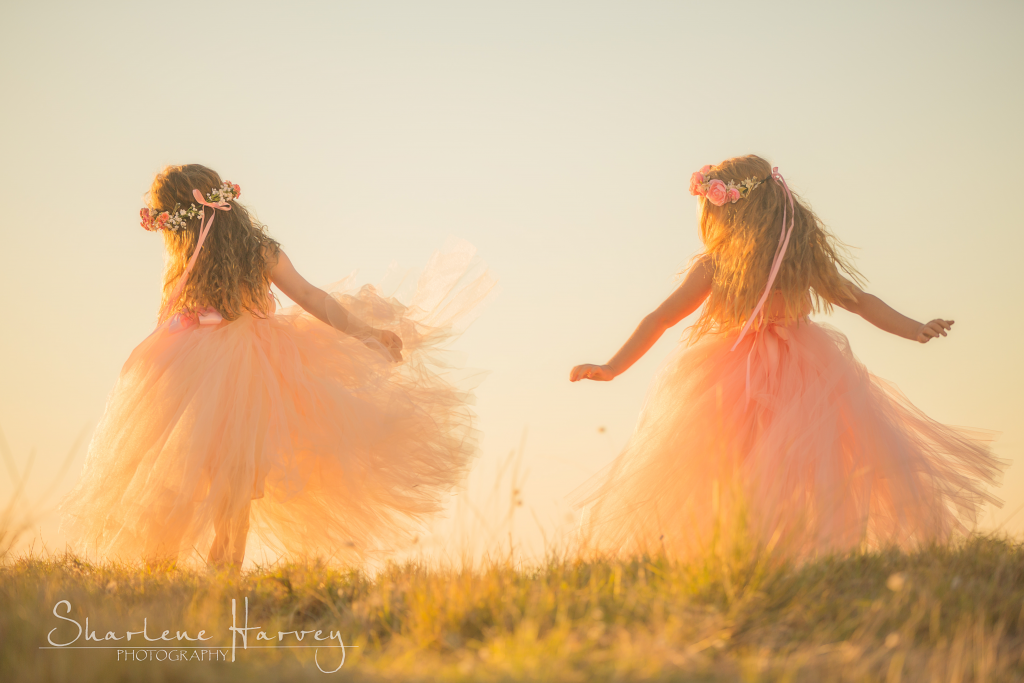 Two girls dancing together on a hill